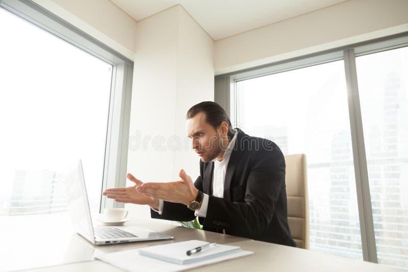 Uomo d'affari sconcertante a causa del problema con il computer portatile fotografia stock libera da diritti