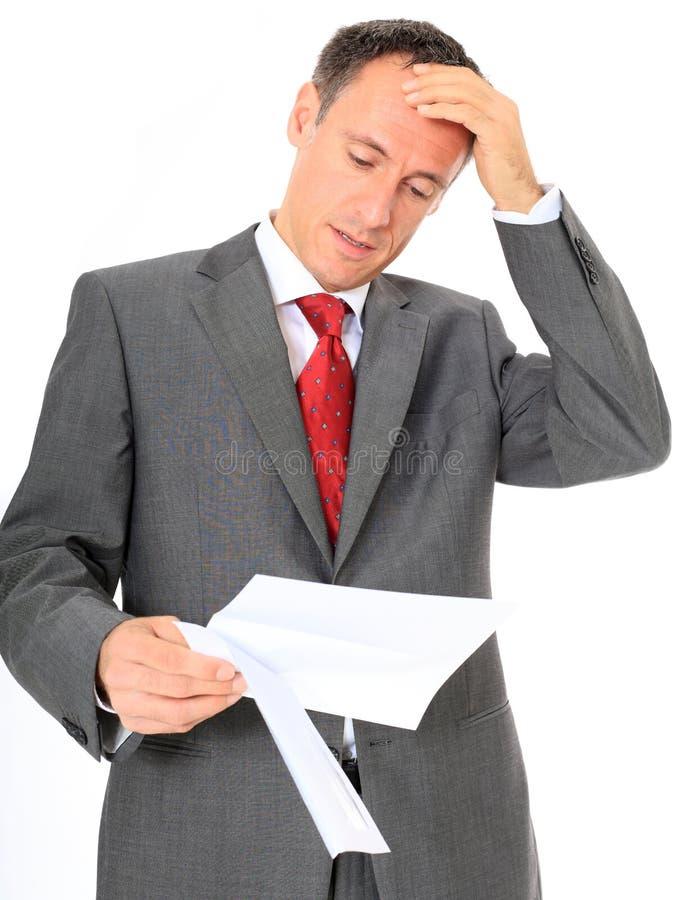 Uomo d'affari scosso che legge una lettera fotografia stock