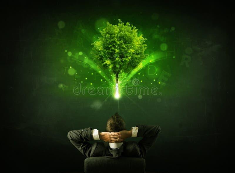 Uomo d'affari in sedia che si siede davanti ad un albero d'ardore immagini stock