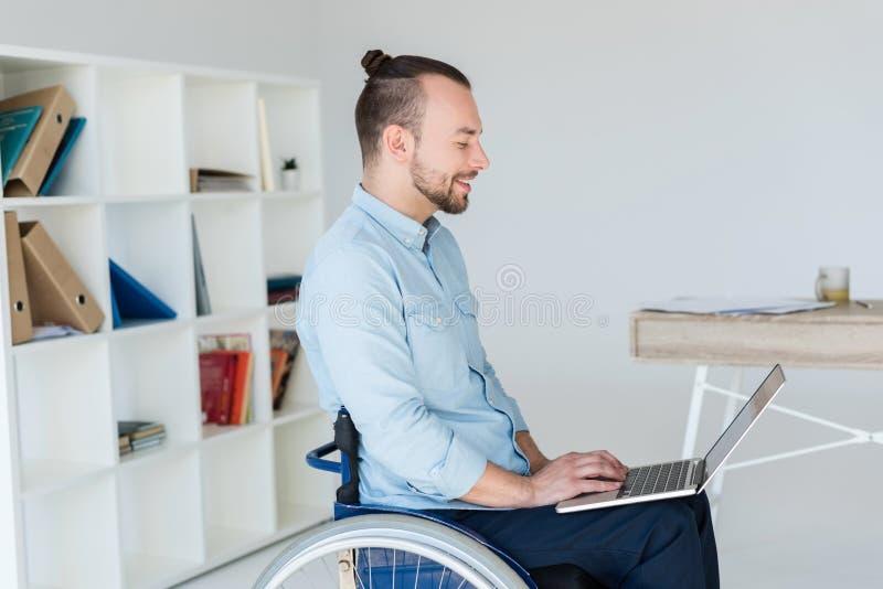 Uomo d'affari in sedia a rotelle che funziona con il computer portatile immagine stock