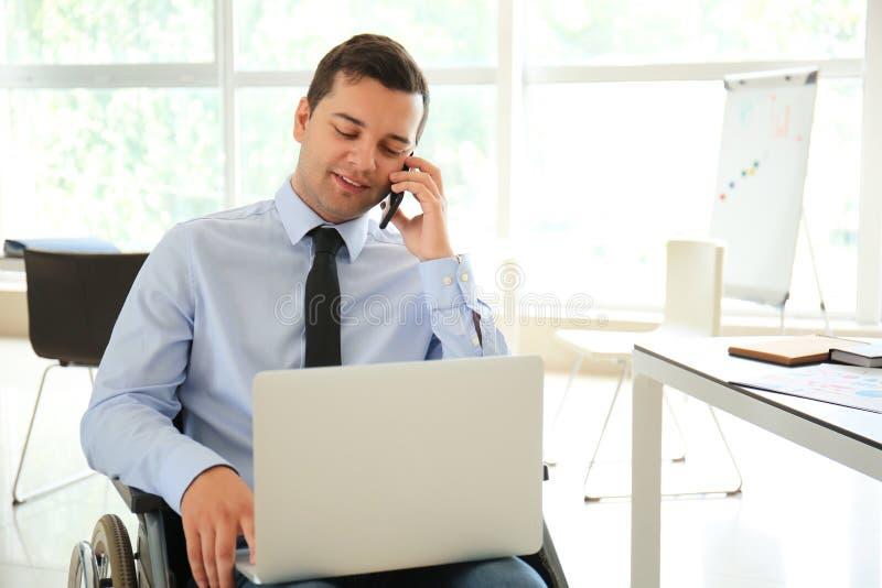 Uomo d'affari in sedia a rotelle che parla sul telefono cellulare in ufficio fotografia stock libera da diritti
