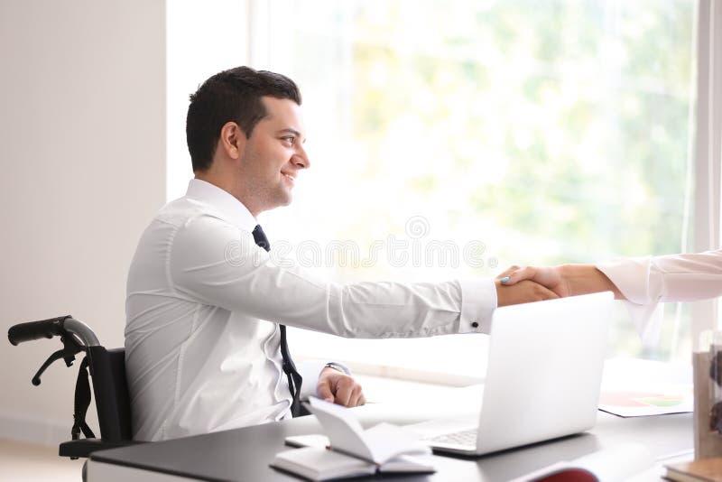 Uomo d'affari in sedia a rotelle che stringe le mani con il collega in ufficio fotografia stock