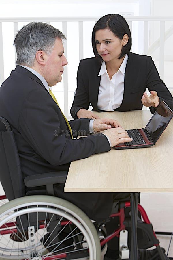 Uomo d'affari in sedia a rotelle con l'assistente immagine stock libera da diritti