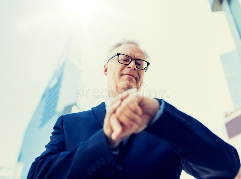 Uomo d'affari senior che controlla tempo sul suo orologio immagini stock