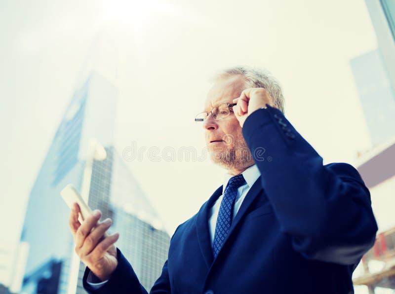 Uomo d'affari senior con lo smartphone in citt? fotografia stock