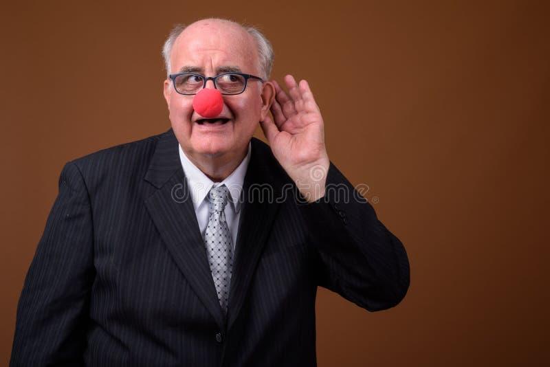 Uomo d'affari senior di peso eccessivo che indossa il naso rosso del pagliaccio fotografia stock libera da diritti