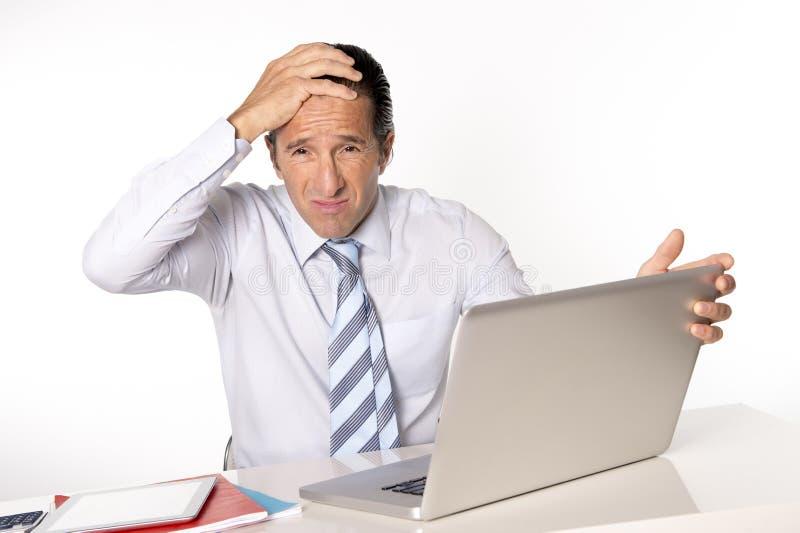 Uomo d'affari senior disperato nella crisi che lavora al computer all'ufficio nello sforzo fotografia stock libera da diritti