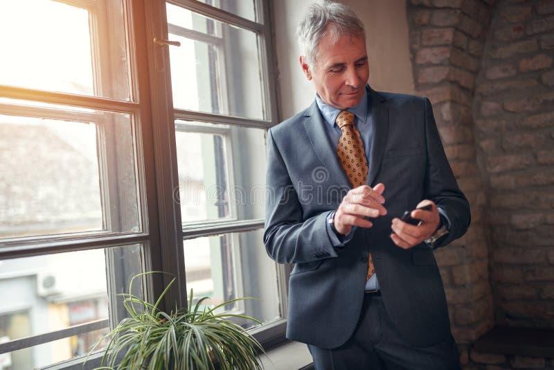Uomo d'affari senior indipendente in vestito con lo smartphone fotografia stock libera da diritti