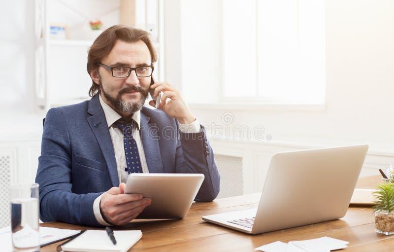 Uomo d'affari serio che comunica sul telefono mobile fotografia stock