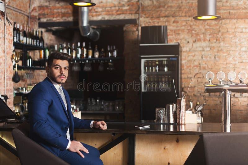 Uomo d'affari serio che si siede al contatore della barra fotografia stock