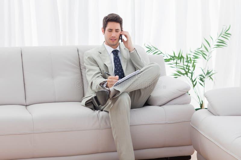 Uomo d'affari serio che si siede sul sofà che chiama con il suo telefono cellulare immagine stock libera da diritti