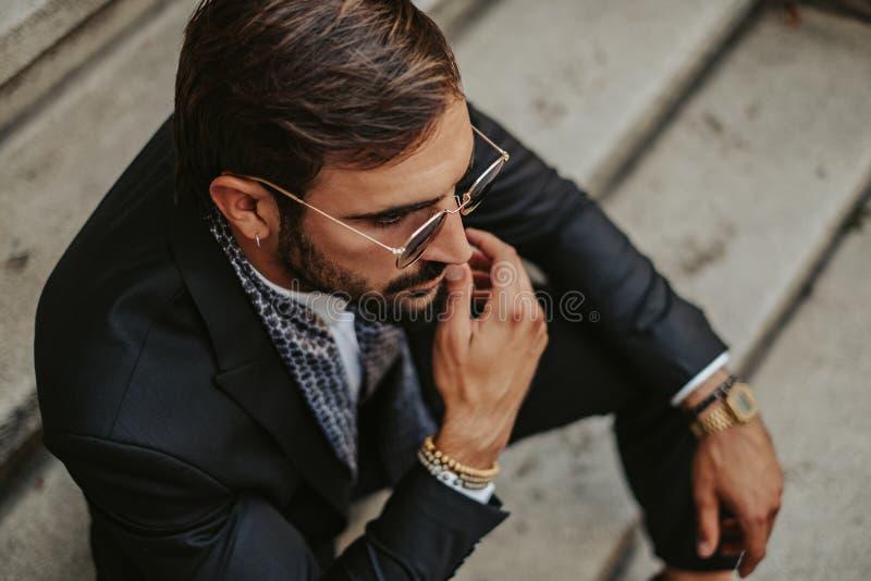 Uomo d'affari serio che si siede sulle scale fotografia stock