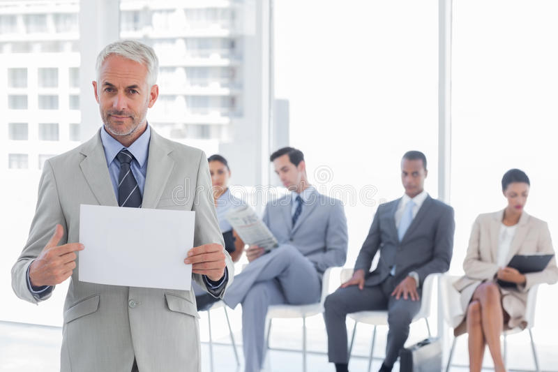 Uomo d'affari serio che tiene un avviso in bianco immagine stock
