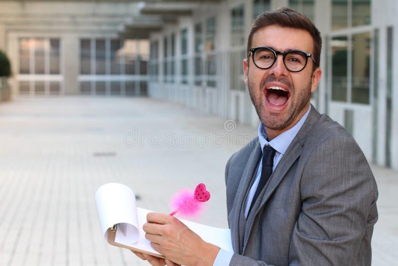 Uomo d'affari sgargiante che prende le note con una penna rosa sveglia immagine stock libera da diritti