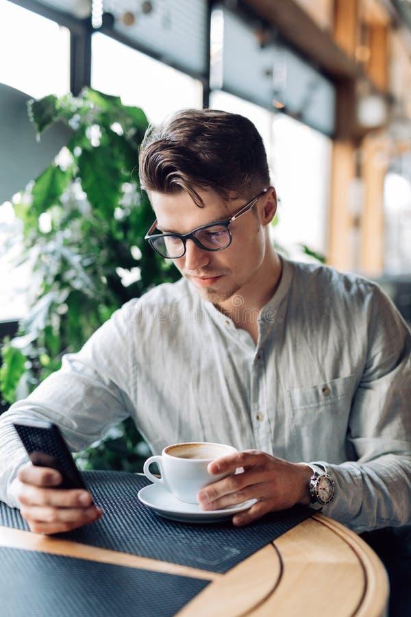 Uomo d'affari sicuro che per mezzo di uno smartphone, avendo tempo rottura al caffè immagine stock