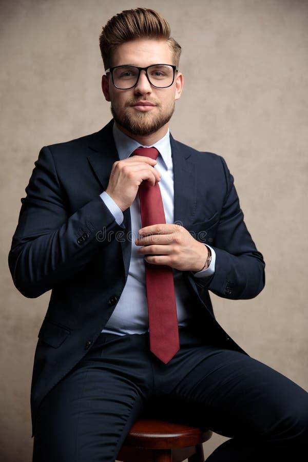 Uomo d'affari sicuro che ripara il suo legame rosso mentre indossando i vetri immagini stock