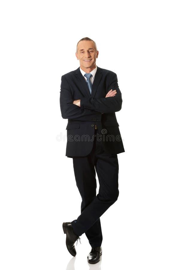 Uomo d'affari sicuro che si leva in piedi con le braccia piegate immagine stock