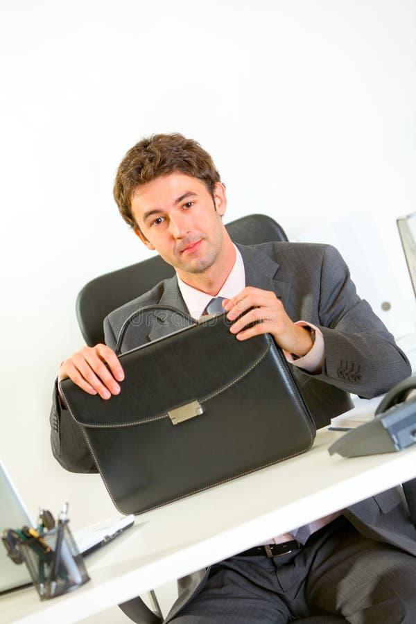 Uomo d'affari sicuro che si siede allo scrittorio con il caso immagine stock
