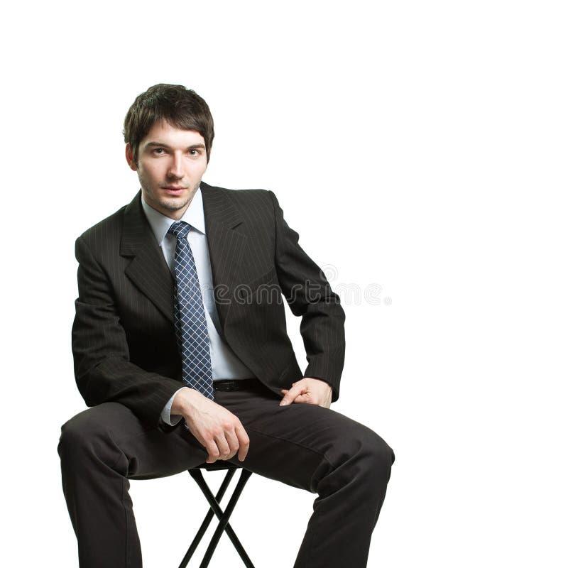 Uomo d'affari sicuro che si siede sulla presidenza immagini stock