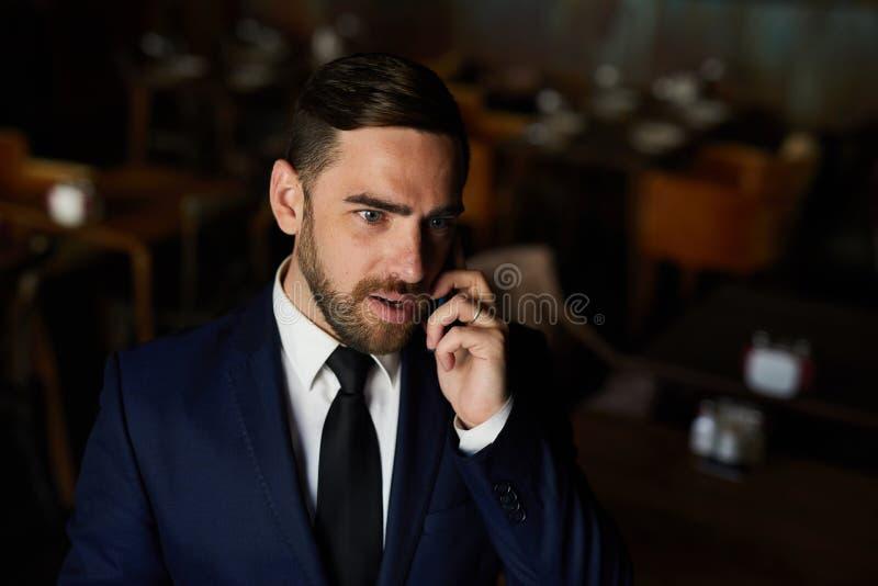 Uomo d'affari sicuro che spiega il suo piano sul telefono immagini stock libere da diritti