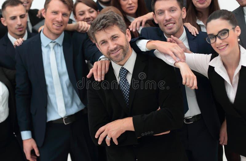 Uomo d'affari sicuro che sta sul fondo del suo gruppo di affari fotografie stock libere da diritti
