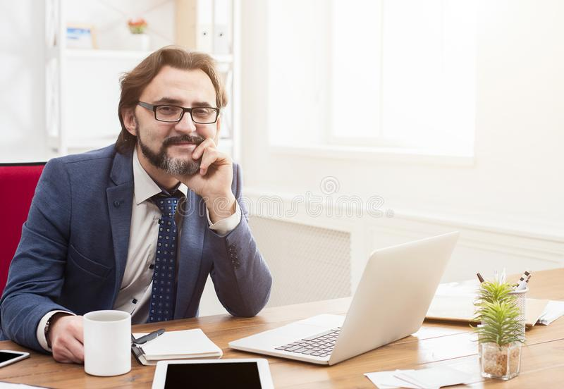 Uomo d'affari sicuro con il computer portatile in ufficio moderno immagini stock libere da diritti