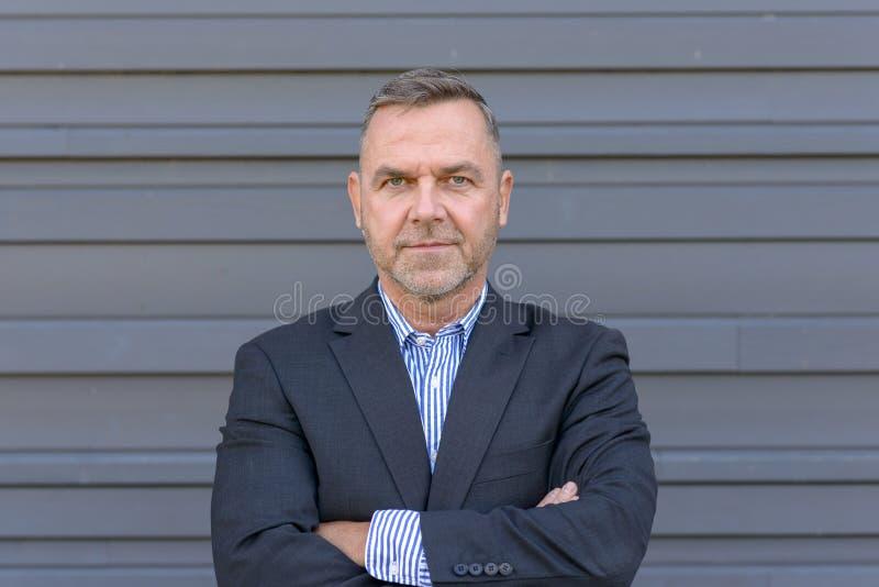 Uomo d'affari sicuro di medio evo sopra gray immagini stock