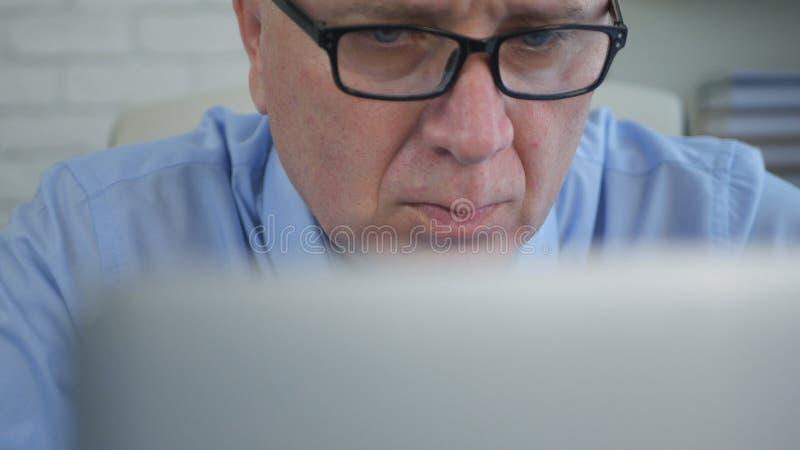 Uomo d'affari sicuro Focused sui documenti del computer portatile immagini stock libere da diritti
