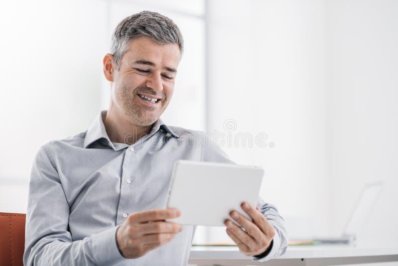 Uomo d'affari sicuro sorridente che utilizza una compressa del touch screen nell'ufficio, sta guardando un video e godere fotografie stock libere da diritti