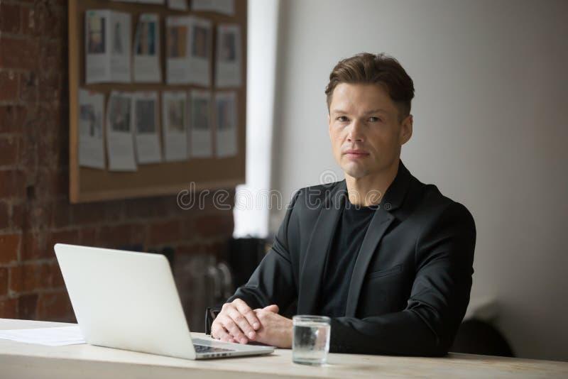 Uomo d'affari sicuro in vestito che si siede con il computer portatile che esamina camma fotografia stock