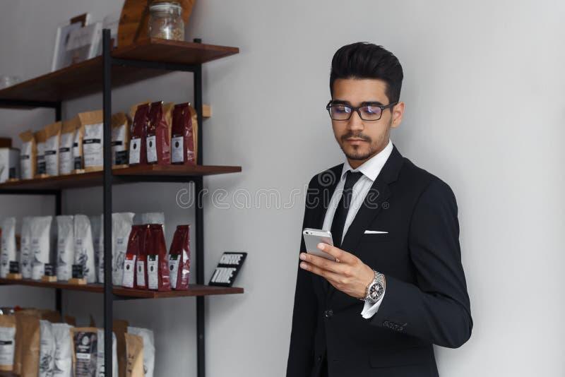 Uomo d'affari sicuro in vestito facendo uso dello smartphone in caffè immagine stock