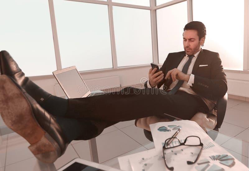 uomo d'affari SMS leggente sul suo smartphone immagini stock libere da diritti