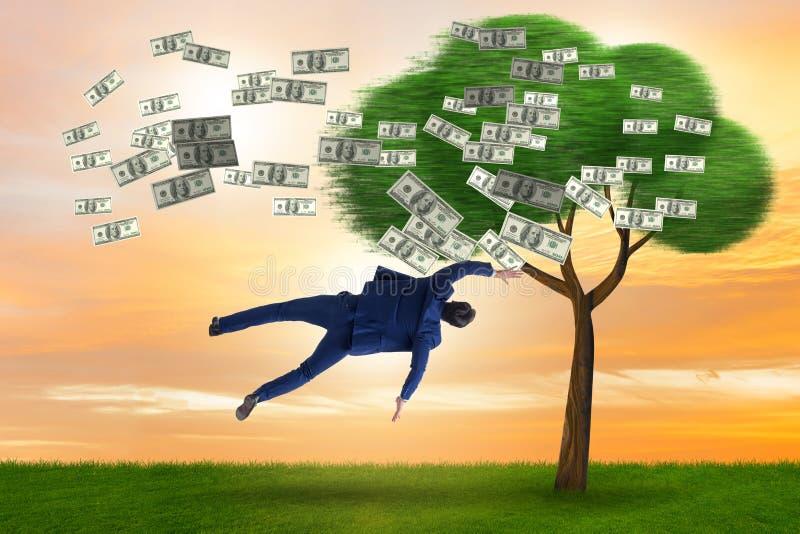 Uomo d'affari soffiato a partire dall'albero dei soldi immagini stock libere da diritti