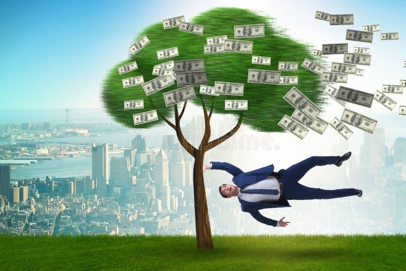 Uomo d'affari soffiato a partire dall'albero dei soldi fotografie stock libere da diritti