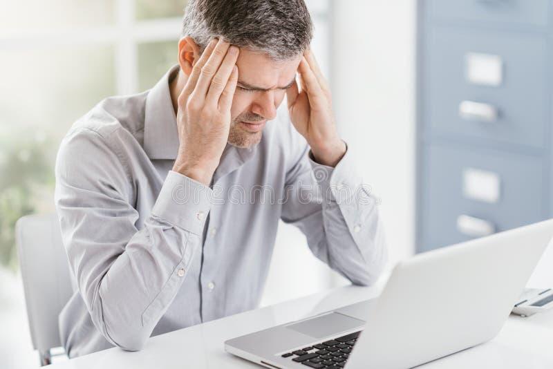 Uomo d'affari sollecitato che lavora alla scrivania e che ha un'emicrania, sta toccando le sue tempie immagini stock libere da diritti