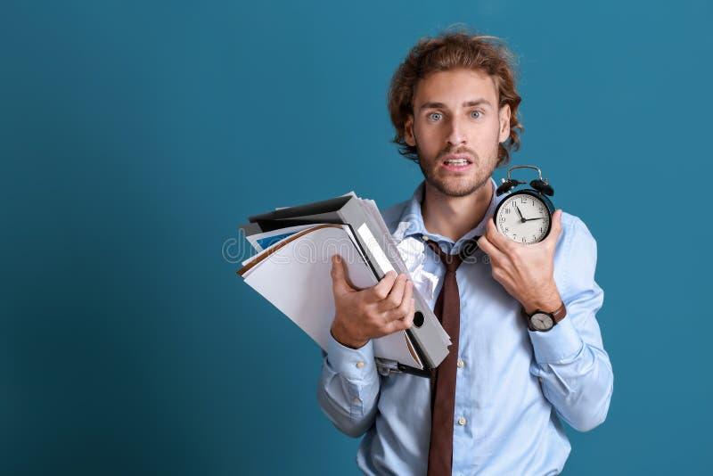 Uomo d'affari sollecitato che prova a rispettare limite sul fondo di colore fotografia stock