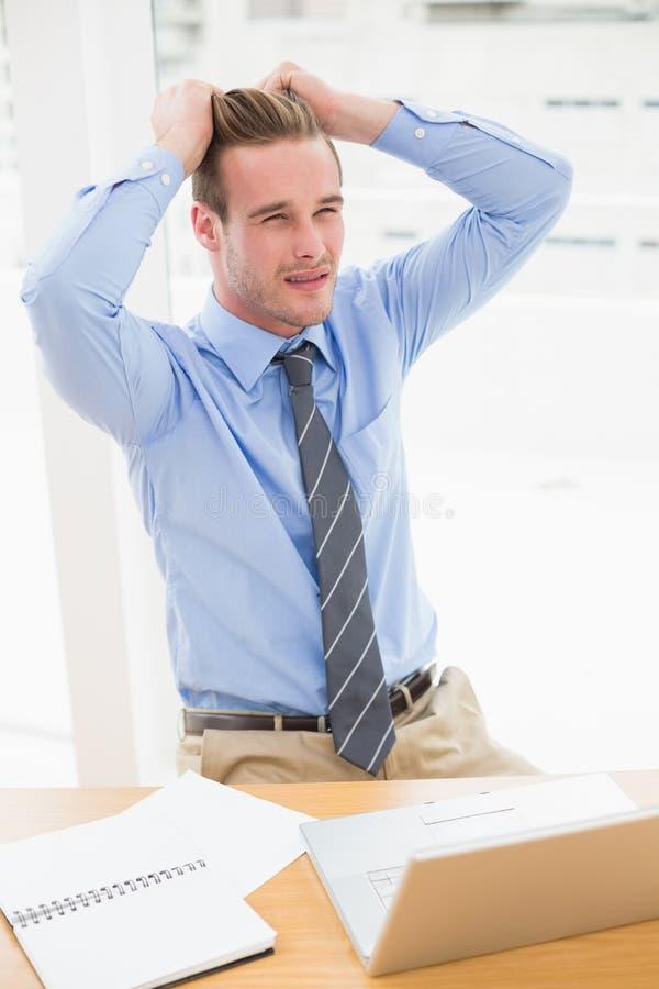 Uomo d'affari sollecitato che si siede al suo scrittorio immagine stock libera da diritti