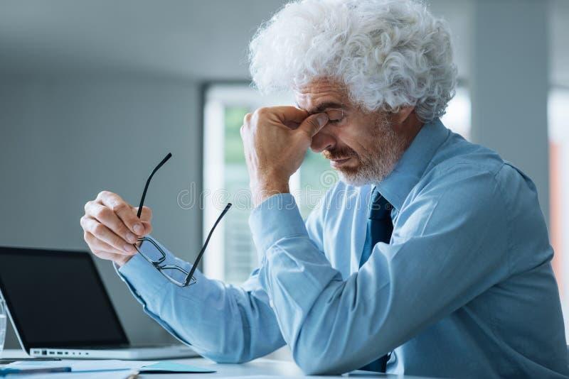 Uomo d'affari sollecitato che si siede alla scrivania fotografie stock