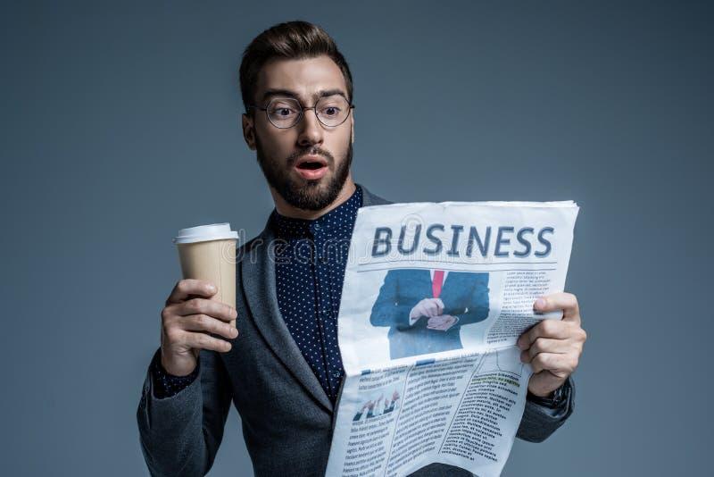 Uomo d'affari sorpreso in vestito e vetri che tengono una tazza di carta e che leggono il giornale di affari fotografia stock libera da diritti