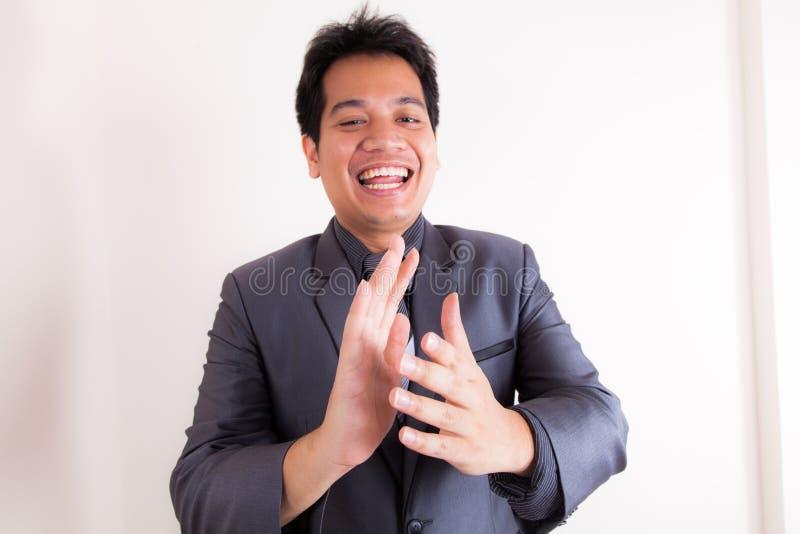 Uomo d'affari sorridente che applaude le sue mani fotografie stock