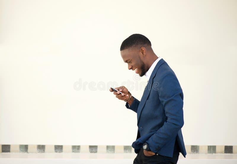 Uomo d'affari sorridente che cammina e che invia messaggio di testo