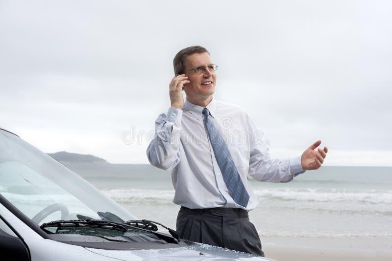 Uomo d'affari sorridente che comunica sul telefono delle cellule fotografia stock