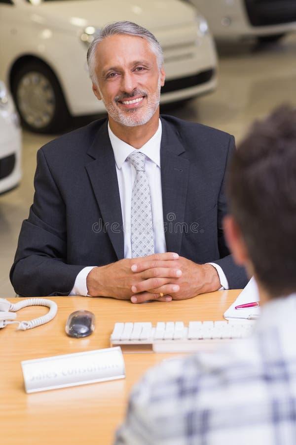 Uomo d'affari sorridente che esamina macchina fotografica fotografia stock libera da diritti