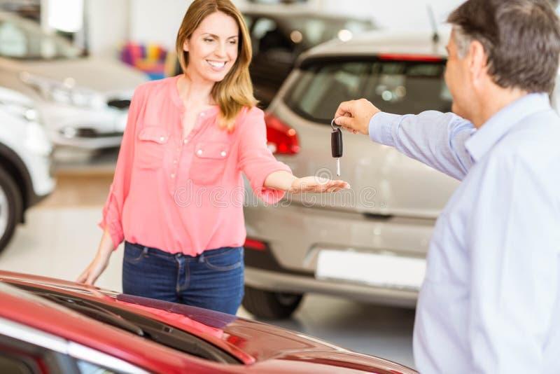 Uomo d'affari sorridente che fornisce chiave dell'automobile al cliente felice immagini stock libere da diritti