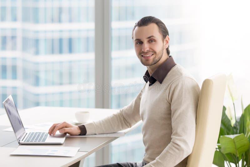 Uomo d'affari sorridente che lavora all'ufficio, esaminando macchina fotografica, usando fotografia stock libera da diritti