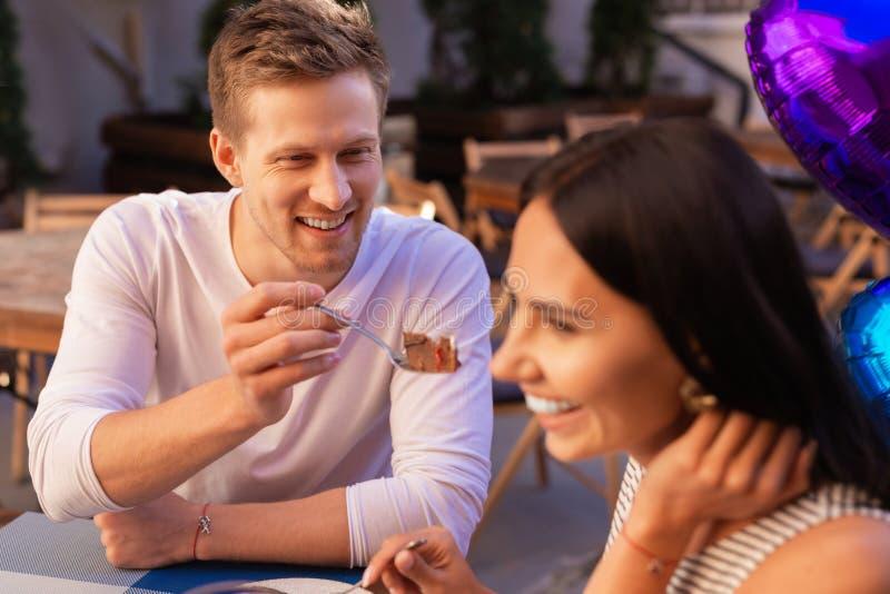 Uomo d'affari sorridente che offre ad un certo dessert la sua giovane moglie fotografia stock libera da diritti