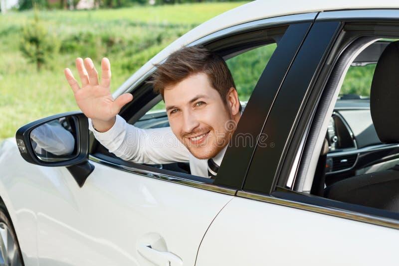Uomo d'affari sorridente che ondeggia la sua mano immagine stock