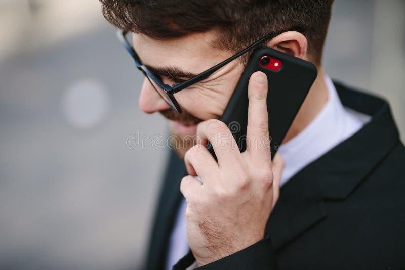 Uomo d'affari sorridente che parla sullo smartphone fotografia stock
