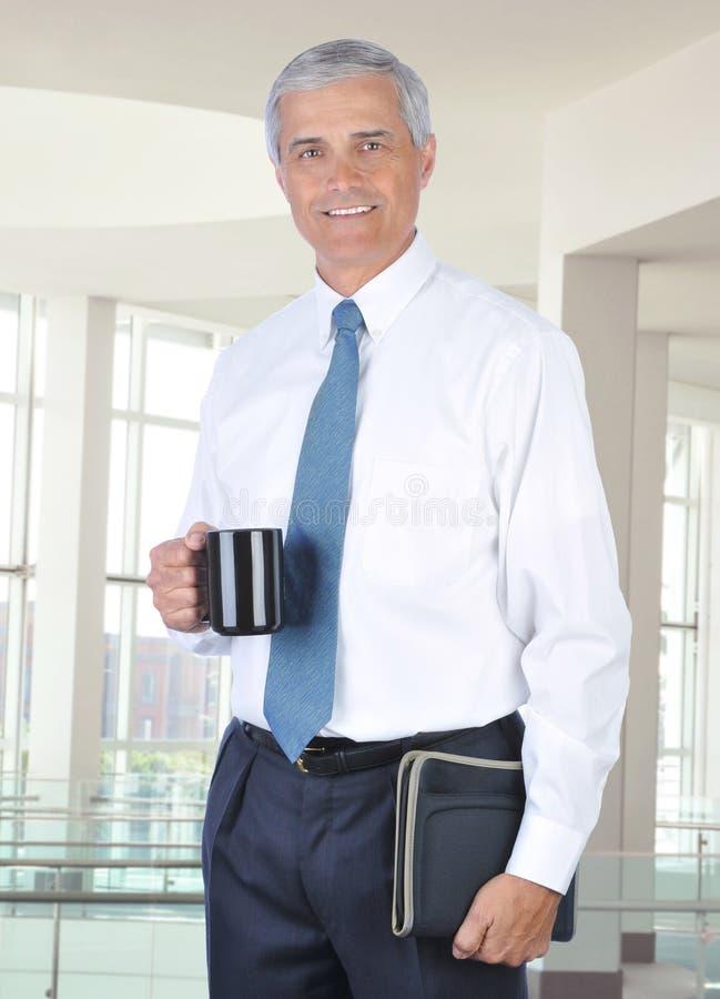 Uomo d'affari sorridente che si leva in piedi nella regolazione dell'ufficio immagine stock