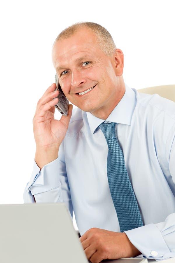 Uomo d'affari sorridente che si siede nell'ufficio dietro lo scrittorio immagini stock libere da diritti